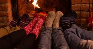 Low section of friends resting legs at fireplace